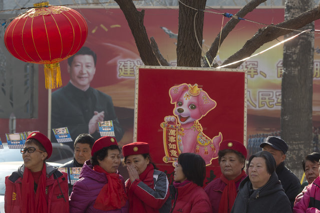 In this Friday, March 2, 2018, photo, residents celebrate lantern festival to mark the end of winter near a mural depicting Chinese President Xi Jinping in a residential compound for retired soldiers in Beijing. (Photo by Ng Han Guan/AP Photo)