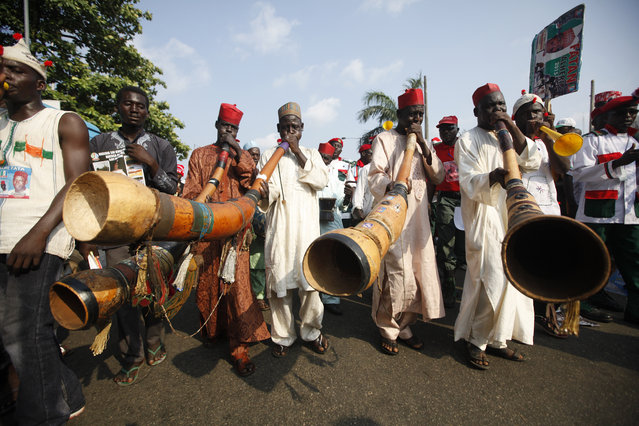 Supporters of presidential aspirant, Rabiu Musa Kwankwaso, sing and play locally made instruments during the All Progressive Congress party convention in Lagos, Nigeria,Wednesday, December 10, 2014. The February 14 presidential vote is expected to be the most closely contested since decades of military rule ended in 1999 in Africa's most populous nation and its biggest oil producer. (Photo by Sunday Alamba/AP Photo)
