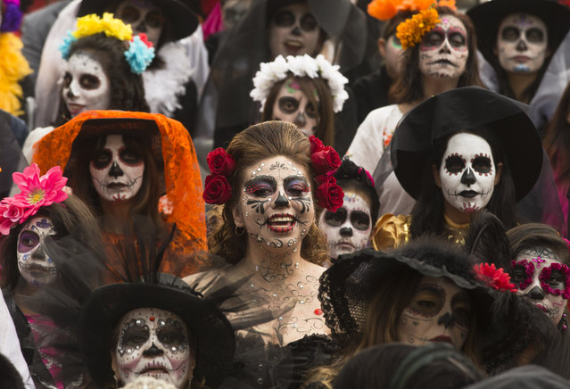 "People dressed as ""Catrinas"" gather for a group photo as they commemorate Day of the Dead, a holiday that honors the deceased, during a Catrina Fest in Mexico City, Sunday, November 1, 2015. The figure of a skeleton wearing an elegant broad-brimmed hat was first done as a satirical engraving by artist Jose Guadalupe Posada sometime between 1910 and his death in 1913. (Photo by Esteban Felix/AP Photo)"