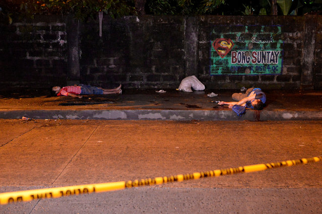 """The bodies of two men, who police said were killed after a drug """"Shabu"""" (Metamphetamine Chloride) buy-bust operation, lie on a sidewalk with revolvers near their hands in Quezon city, Metro Manila, Philippines, October 9, 2016. (Photo by Ezra Acayan/Reuters)"""