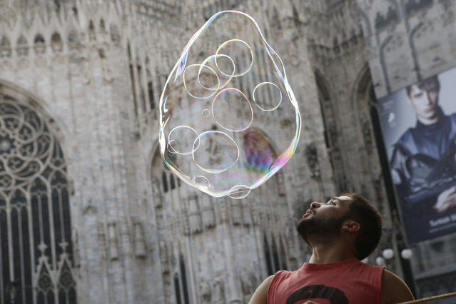 A street artist performs with soap bubbles in front of the Duomo gothic cathedral, in Milan, Italy, Tuesday, October 20, 2015. (Photo by Luca Bruno/AP Photo)