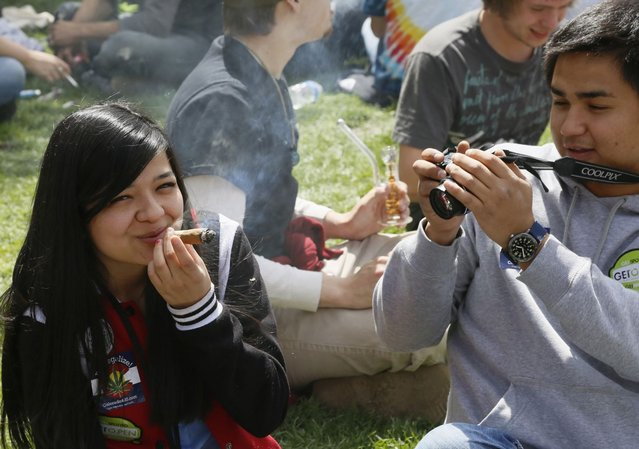 A woman smokes a blunt as a friend takes her picture at the 4/20 marijuana holiday in Civic Center Park in downtown Denver April 20, 2013. (Photo by Rick Wilking/Reuters)