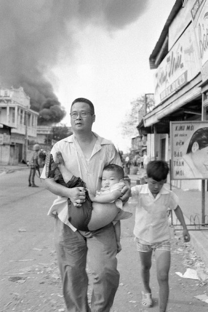 A Vietnamese father runs down a Saigon street with his child on February 2, 1968, as he seeks cover from fierce street-fighting between the Viet Cong and South Vietnamese forces. The child had been wounded. Smoke pours from a burning gasoline station in the background. (Photo by AP Photo)