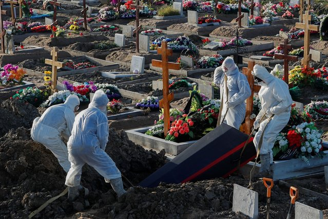 Grave diggers wearing personal protective equipment (PPE) lower a coffin while burying a person in the special purpose section of a graveyard for the coronavirus disease (COVID-19) victims on the outskirts of Saint Petersburg, Russia on November 6, 2020. (Photo by Anton Vaganov/Reuters)