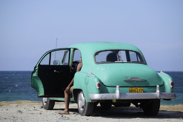 People sit in a U.S.-made car used as a private collective taxi parked near the sea on the outskirts of Havana, May 19, 2013. (Photo by Desmond Boylan/Reuters)