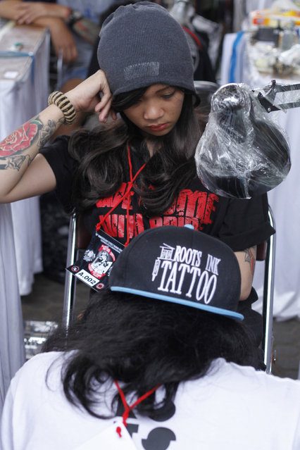 A girl gets a tattoo on her leg during Bandung Body Art Festival at in Bandung, West Java, on December 7, 2014. (Photo by Rezza Estily/JG Photo)