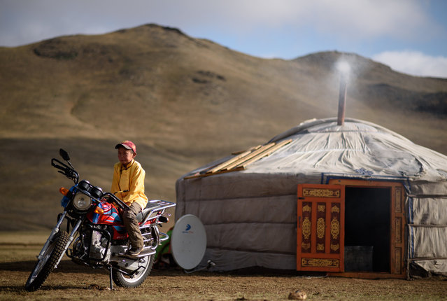 "This picture taken on July 8, 2015 shows 13-year-old jockey Purevsurengiin Togtokhsuren sitting on a motorbike next to his ""yurt"" (R) after taking care of the horses in Khui Doloon Khudag, some 50 kms west of Ulan Bator. (Photo by Johannes Eisele/AFP Photo)"