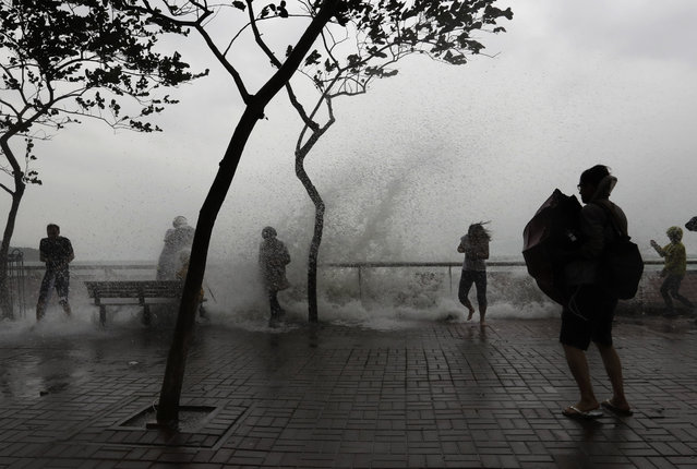 People play with overflown water caused by Typhoon Haima in Hong Kong, Friday, October 21, 2016. (Photo by Kin Cheung/AP Photo)