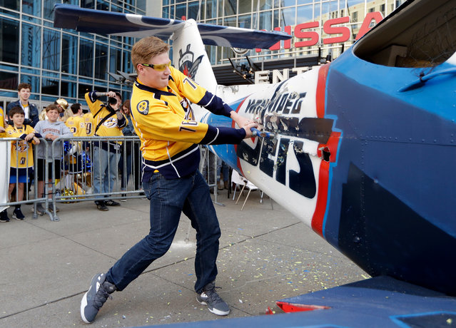 Nashville Predators fan Devin Bradshaw takes a turn beating on a plane painted with the Winnipeg Jets logo and colors outside of Bridgestone Arena before Game 1 of an NHL hockey second-round playoff series between the Predators and the Jets, Friday, April 27, 2018, in Nashville, Tenn. (Photo by Mark Humphrey/AP Photo)