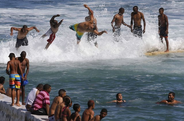 People enjoy the warm summer weather as they celebrate New Year's Day in a tidal pool at Cape Town's St James beach, January 1, 2015. (Photo by Mike Hutchings/Reuters)