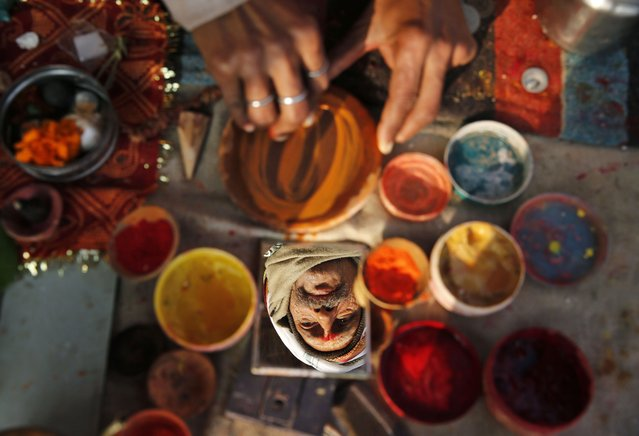 "A Hindu holy man is reflected on a mirror as he prepares a bowl of vermillion powder for devotees near ""Sangam"", the confluence of holy rivers of Ganges, Yamuna and the mythical Saraswati, during the annual traditional fair of Magh Mela in Allahabad, in the northern Indian state of Uttar Pradesh, India, Tuesday, January 6, 2015. (Photo by Rajesh Kumar Singh/AP Photo)"