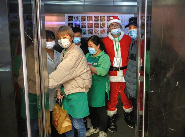 A Chinese worker dressed in a Santa Claus suit as part of Christmas events wears a protective mask to prevent COVID-19 as he and others crowd in an elevator at a shopping mall on December 24, 2020 in Beijing, China. The revival of consumer consumption is expected to continue to boost Chinas economy, which is already showing strong signs of post-pandemic recovery and providing a bright spot for global brands and retailers. (Photo by Kevin Frayer/Getty Images)