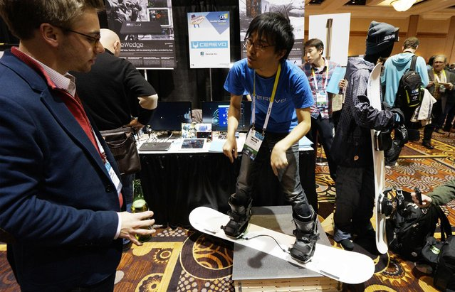 Takuma Iwasa (R) of Cerevo Inc. demonstrates the Xon Snow-1 snowboard analyzing system at the International Consumer Electronics show (CES) in Las Vegas, Nevada January 4, 2015. The Xon uses special bindings and a smartphone app to analyze a snowboarder's technique. (Photo by Rick Wilking/Reuters)