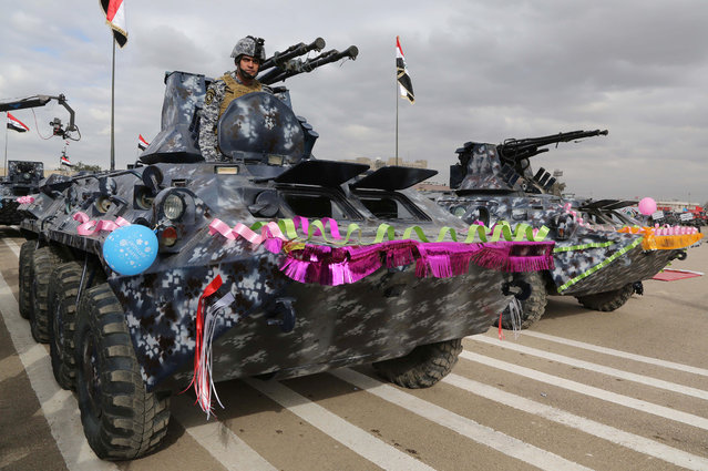 An Iraqi policeman rides an armored vehicle  in a parade marking Police Day in Baghdad, Iraq, Thursday, January 8, 2015. (Photo by Karim Kadim/AP Photo)