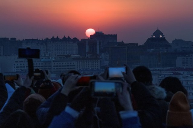 People take pictures the first sunrise of the New Year in Beijing, China, January 1, 2021. (Photo by Thomas Peter/Reuters)