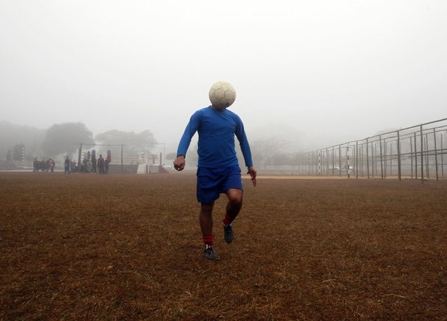 A man controls a ball during his soccer practice in a public park on a foggy morning in Agartala, capital of India's northeastern state of Tripura, January 12, 2015. (Photo by Jayanta Dey/Reuters)