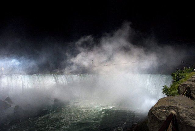 Nik Wallenda nears the middle of his tightrope walk over Niagara Falls as seen from Niagara Falls, Ontario, on Friday, June 15, 2012. Wallenda has finished his attempt to become the first person to walk on a tightrope 1,800 feet across the mist-fogged brink of roaring Niagara Falls. The seventh-generation member of the famed Flying Wallendas had long dreamed of pulling off the stunt, never before attempted. (Photo by Aaron Vincent Elkaim/AP Photo/The Canadian Press)