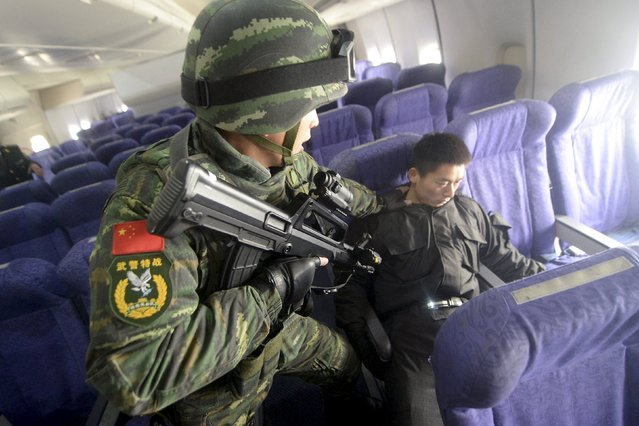An armed paramilitary policeman checks a mock hijacker during an anti-terrorism drill on plane hijacking, on a passenger jet at the Beijing Capital International Airport, in Beijing, China, December 3, 2015. (Photo by Reuters/Stringer)
