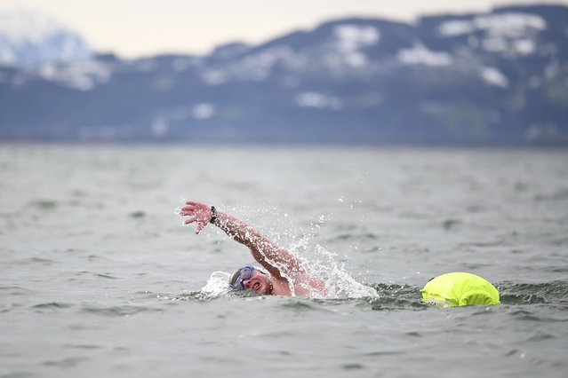 37-year-old ice swimmer Paul Bieber swims in Lake Constance off Wasserburg while being accompanied by lifeguards in a boat in Wasserburg, Germany, Saturday, January 30, 2021. He achieved the new German record in the one-mile swim. He swam the distance of 2210 meters in 41 minutes. (Photo by Felix Kästle/dpa via AP Photo)