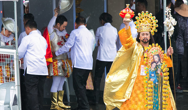A costumed performer raises an image of the Santo Nino (Holy Child) to the crowd hours before the final papal mass of Pope Francis at Quirino Grandstand in Manila, Philippines, Sunday, January 18, 2015. Millions filled Manila's main park and surrounding areas for Pope Francis' final Mass in the Philippines on Sunday. (Photo by Ron Soliman/AP Photo)
