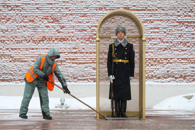 A utility worker clears snow by the Tomb of the Unknown Soldier in Alexander Garden during a snowfall in Moscow, Russia on January 28, 2021. (Photo by Vyacheslav Prokofyev/TASS)