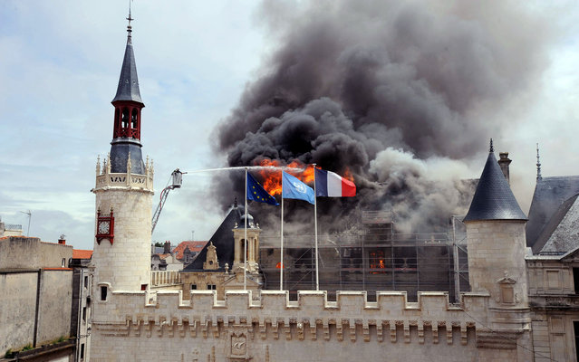 Firemen are at work to extinguish a fire that broke out in La Rochelle city hall, on June 28, 2013 in La Rochelle, western France. The fire swept through the roof of the town hall destroying a part of the listed 15th-Century building. (Photo by Xavier Leoty/AFP Photo)