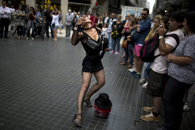 A street artist dances tango in Buenos Aires, Argentina, Tuesday, January 20, 2015. Tango is a partner dance that originated in the 1890's along the Rio de la Plata, the border between Uruguay and Argentina. UNESCO approved in 2009, a joint proposal by the two nations to include the dance in its Intangible Cultural Heritage List. (Photo by Rodrigo Abd/AP Photo)