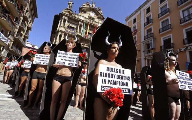 Activists of the People for the Ethical Treatment of Animals (PETA) and Anima Naturalis pro-animal groups stand in coffins that represent the 48 bulls that will be killed during the San Fermin festivities in the Northern Spanish city of Pamplona on July 5, 2013 during an anti-bullfighting protest. The San Fermin festival is a symbol of Spanish culture that attracts thousands of tourists to watch the bull runs despite heavy condemnation from animal rights groups. (Photo by Rafa Rivas/AFP Photo)