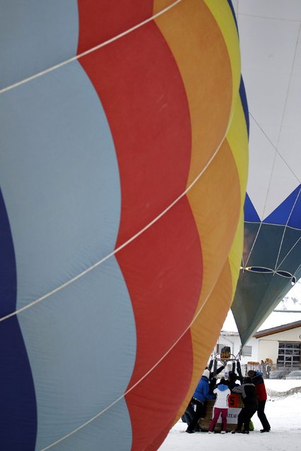 Balloons get ready for take off at the 37th International Hot Air Balloon Week in Chateau-d'Oex, January 24, 2015. (Photo by Pierre Albouy/Reuters)