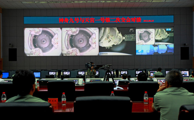Chinese technicians at the Jiuquan Space Center monitor the Shenzhou-9 spacecraft as it prepares to link with the Tiangong-1 module just over a week into a manned space mission which included China's first female astronaut, following an automatic docking, on June 24, 2012. (Photo by STR/AFP Photo via The Atlantic)
