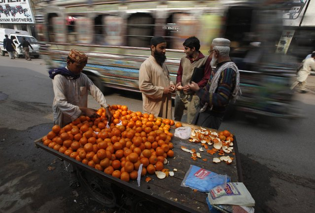 Men eat oranges from a push cart along a road as a vehicle travels past them in Karachi January 22, 2015. (Photo by Akhtar Soomro/Reuters)