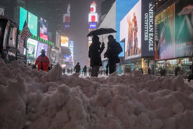 Commuters stand under an umbrella next to snow which was being plowed to the street edge from a walkway in Times Square, New York on January 26, 2015. A massive blizzard slammed into the U.S. Northeast on Monday, canceling thousands of flights. (Photo by Adrees Latif/Reuters)