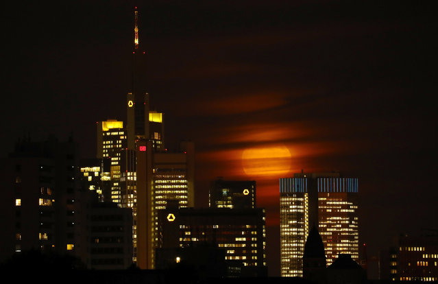 The moon is partly covered by clouds as it rises above the skyline of Frankfurt behind the headquarters of Germany's Commerzbank, in Germany, early evening November 14, 2016. (Photo by Kai Pfaffenbach/Reuters)