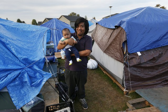 David Yu, 32, poses with his three and a half month old son Joseph, outside his tent at SHARE/WHEEL Tent City 3 outside Seattle, Washington October 8, 2015. (Photo by Shannon Stapleton/Reuters)
