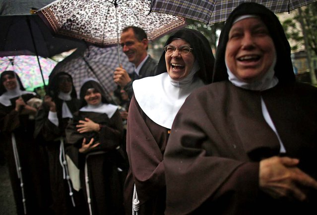 Nuns who rarely leave the Nossa Senhora dos Anjos monastery wait in line in the rain to attend Pope Francis' visit to the Hospital de Sao Francisco de Assis (Hospital of Saint Francis of Assisi) on July 24 in Rio de Janeiro. (Photo by Mario Tama/Getty Images)