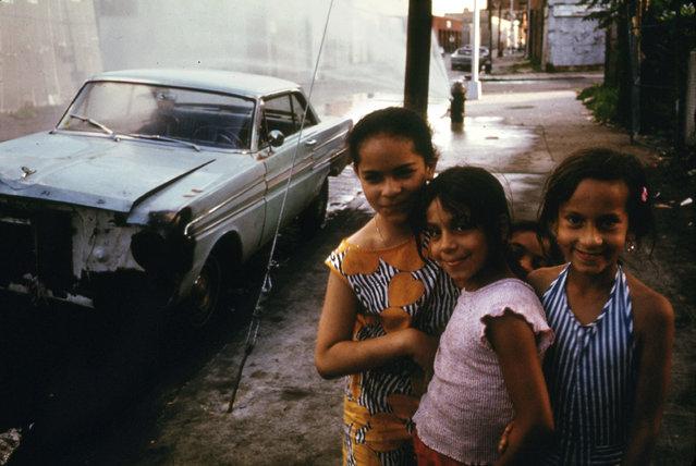A fire hydrant sprays water behind three young girls on Bond Street in Brooklyn, July 1974. (Photo by Danny Lyon/NARA via The Atlantic)