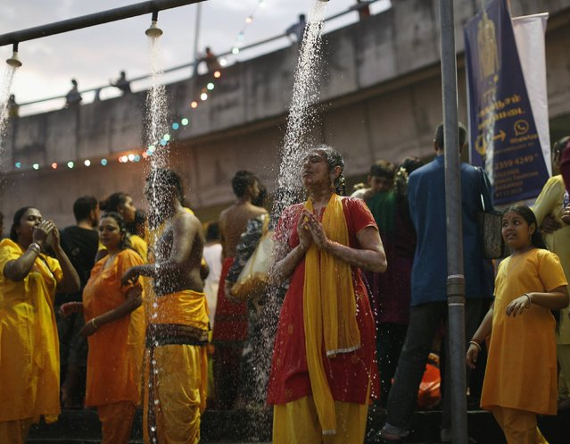 A Hindu devotee prays as she takes a ritual shower before starting her pilgrimage to the Batu Caves temple during Thaipusam in Kuala Lumpur February 2, 2015. (Photo by Olivia Harris/Reuters)