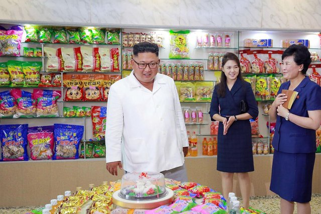 This undated picture released by North Korea' s official Korean Central News Agency (KCNA) on July 26, 2018 via KNS shows North Korean leader Kim Jong Un (C), accompanied by his wife Ri Sol Ju (2nd R), inspecting the Songdowon General Foodstuff Factory in Kangwon Province. (Photo by AFP Photo/KCNA via KNS)