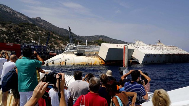 "Tourists, on a ferry outside Giglio harbor in Italy on August 8, 2013, take pictures of the capsized cruise liner Costa Concordia as it lies surrounded by containers called ""sponsons"" as part of the salvage plan to remove the wreck of the ship. Insurance industry payouts related to last year's sinking of the cruise liner have continued to rise and are likely to top $1.1 billion as salvaging of the wreck continues, reinsurer Munich Re said. (Photo by Stefano Rellandini/Reuters)"