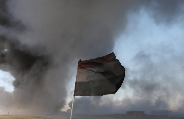 An Iraqi flag is seen in front of oilfields burned by Islamic State fighters in Qayyara, south of Mosul, Iraq November 23, 2016. (Photo by Goran Tomasevic/Reuters)