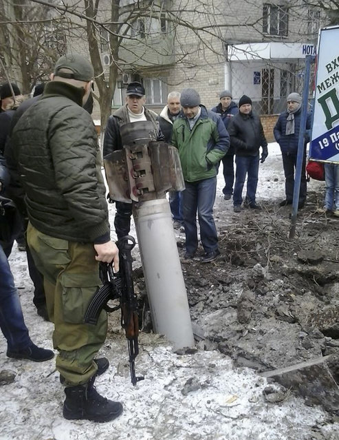 Residents look at an unexploded rocket in a living area in Kramatorsk, Ukraine, Tuesday, February 10, 2015.  Ukrainian President Petro Poroshenko told Parliament that Russian-backed rebels launched an artillery strike on the town of Kramatorsk, which is more than 50 kilometers (30 miles) away from the front line. (Photo by AP Photo)