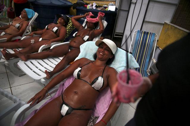 "Women wearing their masking tape bikinis, sunbathe to have the perfect bikini mark (""marquinha"" in Portuguese), at the Erika Bronze spa in Rio de Janeiro, Brazil, November 22, 2016. (Photo by Pilar Olivares/Reuters)"