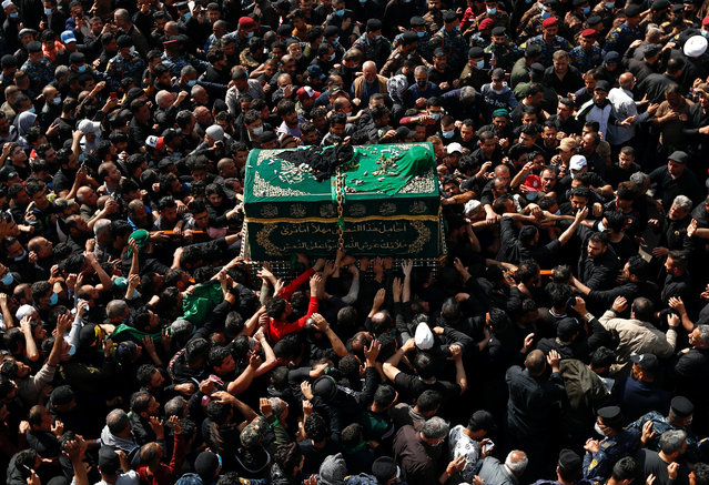 Shiite worshippers carry a symbolic coffin at the golden-domed shrine of Imam Moussa al-Kadhim, who died at the end of the 8th century, during the annual commemoration of his death, in Baghdad, Iraq, Wednesday, March 10, 2021. (Photo by Hadi Mizban/AP Photo)