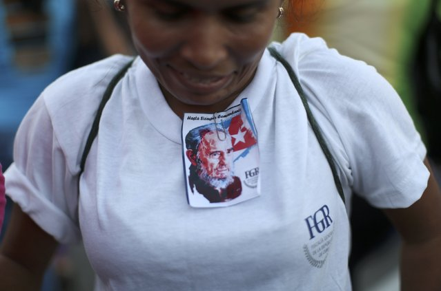 A mourner wears an image of Cuba's late President Fidel Castro clipped to her shirt as she and others pay tribute to Castro at a rally at Revolution Square in Havana, Cuba, November 29, 2016. (Photo by Alexandre Meneghini/Reuters)