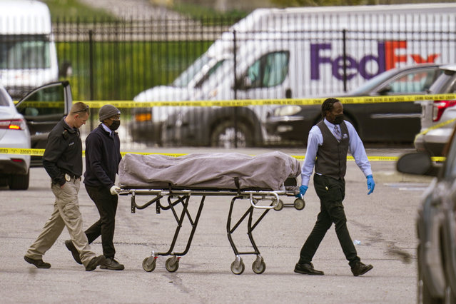 A body is taken from the scene where multiple people were shot at a FedEx Ground facility in Indianapolis, Friday, April 16, 2021. A gunman killed several people and wounded others before taking his own life in a late-night attack at a FedEx facility near the Indianapolis airport, police said. (Photo by Michael Conroy/AP Photo)