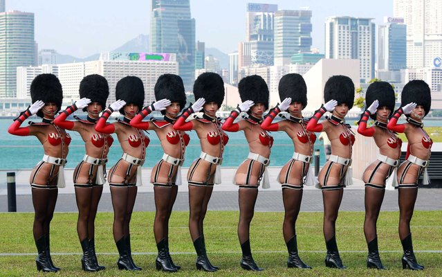 """A line of """"Crazy Horse"""" dancers in full regalia pose for photographers in Hong Kong, China, on September 11, 2012. (Photo by Ricky Ngan/AFP Photo/United Events)"""