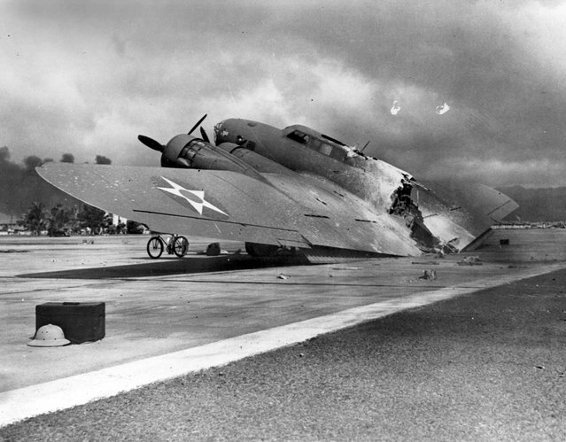 A wrecked U.S. Army Air Corps B-17C bomber lies at Hickam Air Field, following the end of the Japanese raid on Pearl Harbor, Hawaii, U.S. December 7, 1941. This plane, piloted by Captain Raymond T. Swenson, was one of those that arrived during the raid after flying in from California. It was hit by a strafing attack after landing and burned in half. (Photo by Reuters/U.S. Navy/National Archives)