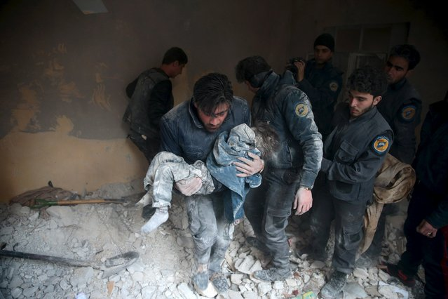 A man carries a child that survived from under debris in a site hit by what activists said were airstrikes carried out by the Russian air force in the town of Douma, eastern Ghouta in Damascus, Syria January 10, 2016. (Photo by Bassam Khabieh/Reuters)