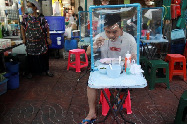 A person eats at a street food stall, amid the outbreak of the coronavirus disease (COVID-19) in Bangkok, Thailand, April 27, 2021. (Photo by Soe Zeya Tun/Reuters)