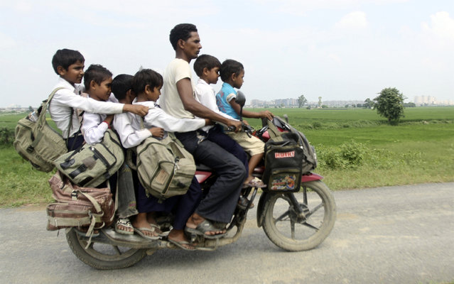 A man rides a motorcycle carrying six children on their way back home from school at Greater Noida in the northern Indian state of Uttar Pradesh September 10, 2010. (Photo by Parivartan Sharma/Reuters)